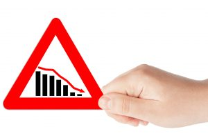 Downward trend concept. Chart on a Triangular red road signs with hand on a white background